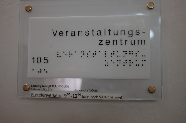 Room sign from Kunstuniversität Graz with writing in braille.